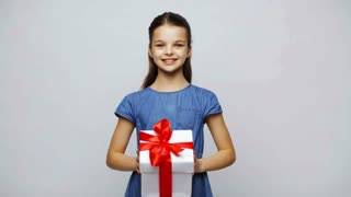 childhood, people, holidays, christmas and birthday concept - happy smiling girl shaking gift box