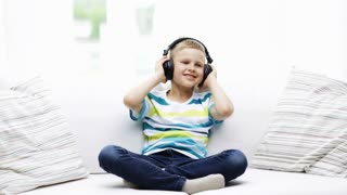 childhood, technology, music and happiness concept - smiling little boy in headphones listening to music, sitting on sofa at home