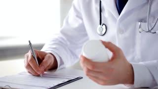 closeup of male doctor making a prescription