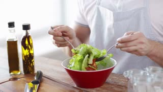 cooking and home concept - close of male hands mixing salad in a bowl