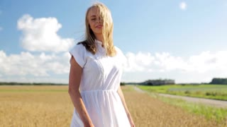 country, nature, summer holidays, vacation and people concept - smiling young woman in white dress dancing and spinning around on cereal field in slow motion mode