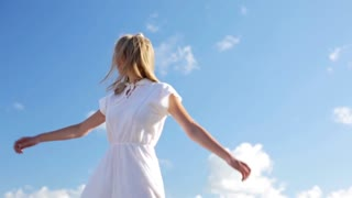 country, nature, summer holidays, vacation and people concept - smiling young woman in white dress dancing and spinning around over blue sky in slow motion mode