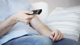 drinks, television, leisure and people concept - close up of man drinking beer and changing tv channels with remote control at home