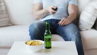 drinks, television, leisure and people concept - close up of man with beer and  chips changing tv channels by remote control at home