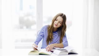 education and home concept - happy smiling student girl with books, reading and making notes