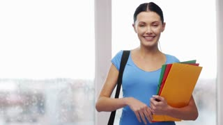 education and people concept - smiling student with bag and folders showing thumbs up