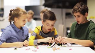 education, children, technology, science and people concept - group of happy kids learning to create robots at robotics lesson and making high five gesture