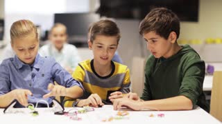 education, children, technology, science and people concept - group of smiling kids learning to create robots at robotics school lesson