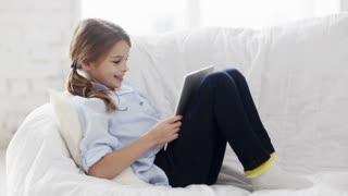 education, free time, technology and internet concept - little student girl with tablet pc at home