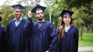 education, graduation and people concept - group of happy international students in mortar boards and bachelor gowns celebrating success
