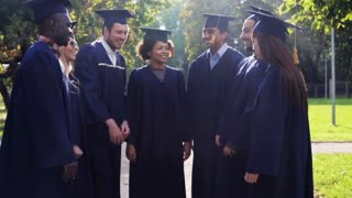 education, graduation and people concept - group of happy international students in mortar boards and bachelor gowns putting hands on top
