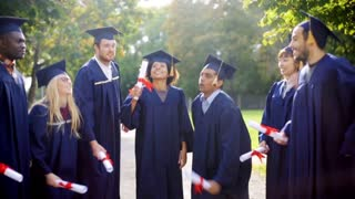 education, graduation and people concept - group of happy international students in mortar boards and bachelor gowns with diplomas celebrating success