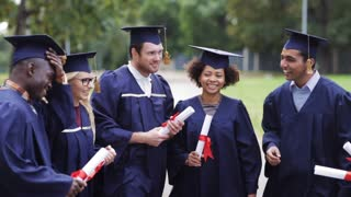 education, graduation and people concept - group of happy international students in mortar boards and bachelor gowns with diplomas talking and laughing