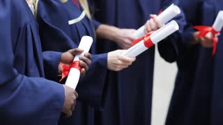 education, graduation and people concept - group of international students in bachelor gowns holding diploma scrolls