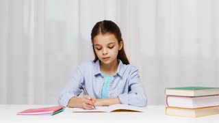 education, people, children and learning concept - bored school girl with books writing to notebook at home