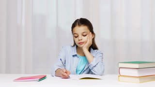 education, people, children and learning concept - girl hand writing math task to notepad at school