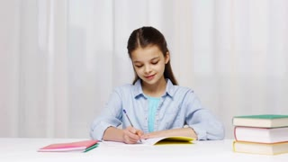 education, people, children and learning concept - girl writing math task to notepad at school
