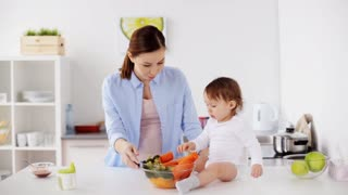 family, food, child, eating and parenthood concept - happy young mother mother offering boiled vegetables to her baby at home kitchen
