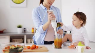family, food, child, eating and parenthood concept - happy young mother with blender cooking puree for her baby sitting on table at home kitchen