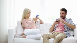 family, technology, relationship difficulties and people concept - couple with smartphones texting at home