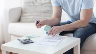 finances, business, economy and people concept - close up of man with calculator and bills counting money at home