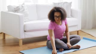 fitness, sport, yoga, training and people concept - happy african woman in lotus pose exercising on mat at home