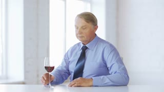 food, drink, leisure, beverages concept - expert in suit and tie with a glass of red wine