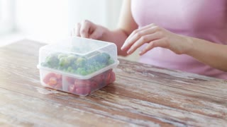 food, storage, dieting and people concept - close up of woman eating vegetables from container at home kitchen