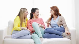 friendship, communication and happiness concept - three smiling girlfriends having a talk at home