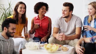 friendship, leisure, fast food, unhealthy eating and celebration concept - happy friends with drinks and snacks clinking bottles at home
