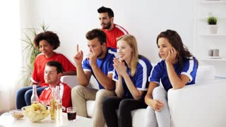 friendship, leisure, sport and entertainment concept - happy friends or football fans watching soccer at home