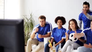 friendship, leisure, sport, people and entertainment concept - friends or football fans watching soccer game on tv at home