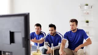friendship, sports, people and entertainment concept - happy male friends or football fans watching soccer at home