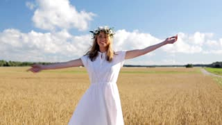 happiness, nature, summer holidays, vacation and people concept - smiling young woman in wreath of flowers dancing and spinning around on cereal field in slow motion mode