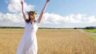 happiness, nature, summer holidays, vacation and people concept - smiling young woman in wreath of flowers dancing and spinning around on cereal field