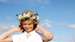 happiness, nature, summer holidays, vacation and people concept - smiling young woman in wreath of flowers enjoying sun outdoors outdoors in slow motion mode