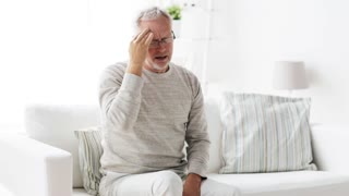 health care, pain, stress, age and people concept - senior man suffering from headache at home