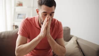 healthcare, flu, hygiene and people concept - sick man blowing nose to paper napkin at home
