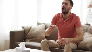 healthcare, flu, hygiene and people concept - sick man blowing nose to paper wipe or napkin at home