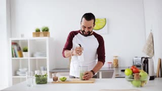 healthy eating, cooking, vegetarian food, diet and people concept - happy young man with blender preparing vegetable smoothie and drinking it at home kitchen