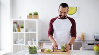 healthy eating, cooking, vegetarian food, diet and people concept - happy young man with blender preparing vegetable smoothie at home kitchen