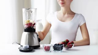healthy eating, cooking, vegetarian food, dieting and people concept - smiling young woman with berries and fruits pouring milk to blender and blending shake at home