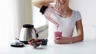 healthy eating, cooking, vegetarian food, dieting and people concept - smiling young woman with berries pouring milk shake from blender jar to glass at home