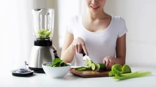 healthy eating, cooking, vegetarian food, dieting and people concept - smiling young woman with blender and green vegetables for detox shake or smoothie at home