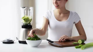 healthy eating, cooking, vegetarian food, dieting and people concept - smiling young woman with blender and green vegetables making detox shake or smoothie at home