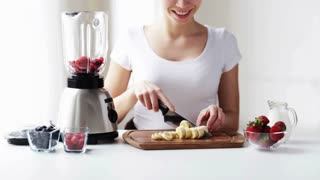 healthy eating, cooking, vegetarian food, dieting and people concept - smiling young woman with blender chopping banana for fruit shake at home