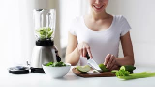healthy eating, cooking, vegetarian food, dieting and people concept - smiling young woman with blender chopping green vegetables for detox shake or smoothie at home