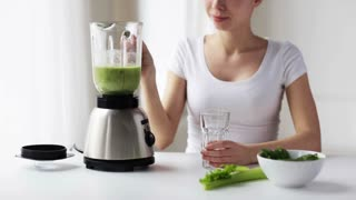healthy eating, cooking, vegetarian food, dieting and people concept - smiling young woman with green vegetables pouring detox shake or smoothie from blender jar to glass at home