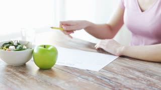 healthy eating, dieting and people concept - close up of young woman hands writing diet plan at home
