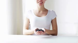 healthy eating, dieting, vegetarian food and people concept - close up of young woman showing blueberries at home